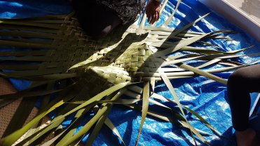 Maata weaving the kete
